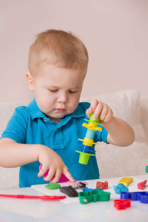 modeling clay: Child with colorful clay. Toddler playing and creating toys from play dough. Boy molding modeling clay.