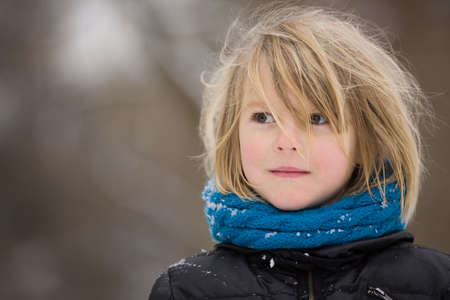 pre teen boy: Portrait of adorable little kid boy with long blond hair outdoors. Child with blue scarf walking on a windy day