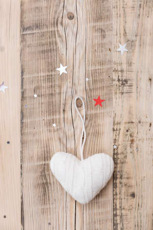 chrstmas: Knitted white heart Christmas decoration on retro wooden background with sparkling stars. Holiday season and celebration concept.