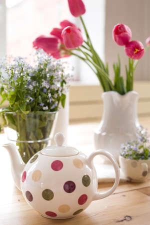 Teapot With Dots And Vases With Beautiful Spring Flowers On The