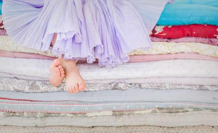 동화는 완두콩에 공주. 라일락 tatu 치마 높은 침대에 앉아있는 어린 소녀. 맨발이 여자면. 다채로운 매트리스의 더미에 앉아 어린 소녀의 다리.