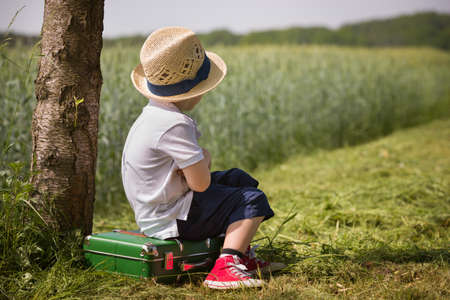 Cute little kid boy in shorts, white polo and straw hat sits on his green suitcase in a field near a tree waiting for a bus. summer portrait of a small child in profile, retro style. Ready to travel.