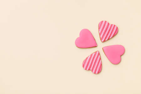 Top view on three little gingerbread cookies in shape of hearts on light yellow background. Flay layout. Love, Valentiness day concept Stock Photo