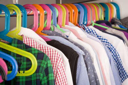 어린이 옷 방에 옷걸이. 옷장에 소년 옷을 입힌 옷장. 쇼핑 및 소비 개념입니다. 옷걸이 옷걸이 옷걸이에 정렬합니다. 아이들을위한 다채로운 옷장입니