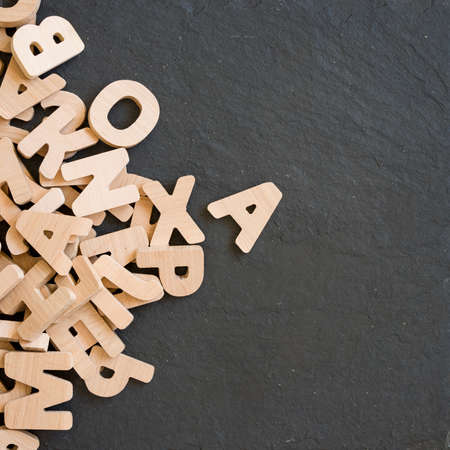 letterpress type: Many wooden letters on black background. Copy space. Stock Photo