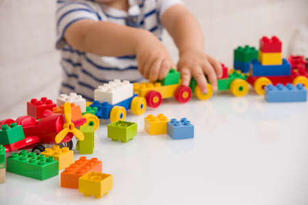 Close up of child's hands playing with colorful plastic bricks at the table. Toddler having fun and building out of bright constructor bricks. Early learning.  stripe background. Developing toys 스톡 콘텐츠