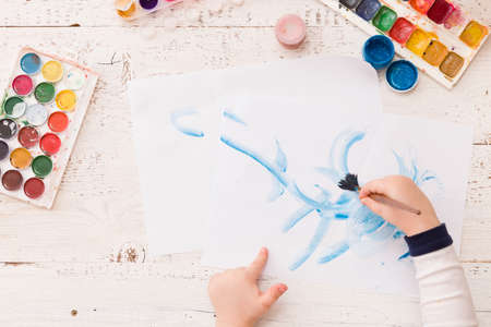 Top view on childs hands drawing with paint brush on paper. Colorful picture made by a toddler boy. Creative ideas and learning. Education concept. Stock Photo