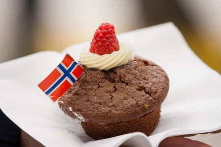 17th: A chocolate cupcake  with Norwegian flag on a white napkin. Celebration ofr May 17th.
