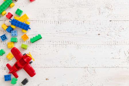 흰색 나무 배경에 화려한 장난감 벽돌에 상위 뷰. 테이블에 장난감