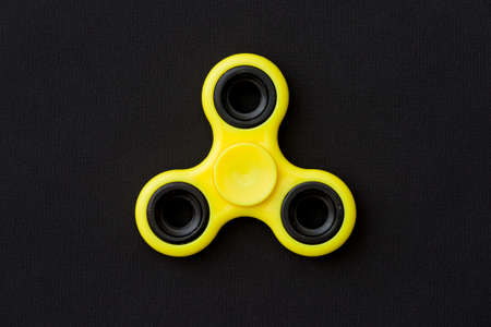 Yellow fidget spinner device on black background. Top view. Playing with a yellow hand spinner fidget toy