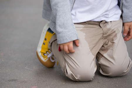Un ragazzino che fa pipì sui pantaloni per strada - Concetto di bagnare il letto. Bambino pipì sui vestiti. Archivio Fotografico - 81923368