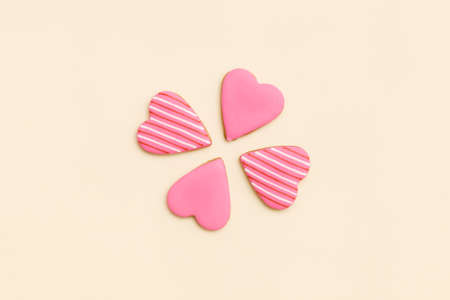 Top view on four little pink gingerbread cookies in shape of hearts on light yellow background. Flay layout. Love, Valentiness day concept