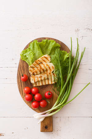 Grilled slices of homemade halloumi cheese with green salad, fresh herbs and organic tomatoes. Fried halloumi cheese with grill marks on wooden background, top view, close-up Stock Photo