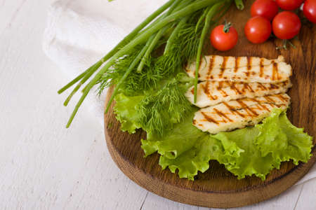 Grilled slices of homemade halloumi cheese with green salad, fresh herbs and organic tomatoes.Fried halloumi cheese with grill marks on white wooden background, top view