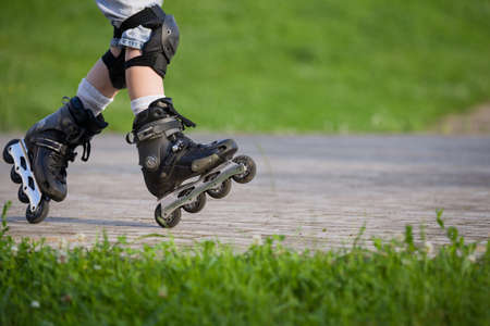 Closeup view of black roller skates or rollerblading. Roller skate legs of a child in the park. Boys legs in roller blades. Stock Photo