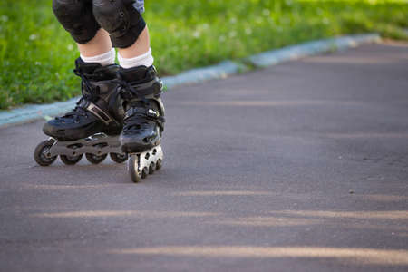 skate park: Closeup view of black roller skates or rollerblading. Roller skate legs of a child in the park. Boys legs in roller blades. Stock Photo