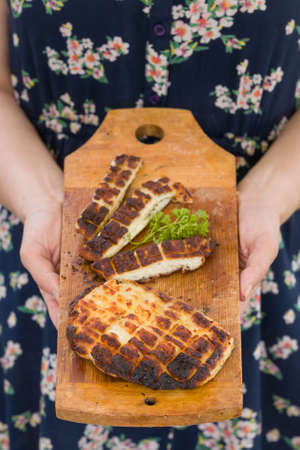 Top view on two grilled slices of homemade halloumi cheese on wooden borad in womans hands. Outdoors. Grilling season. Healthy eating.
