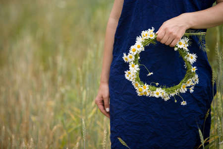 holding hands while walking: Closeup of young womans hands holding wreath with wild flowers while walking on wheat or rye field on a summer day. Countryside landscape. Girl with chamomiles.