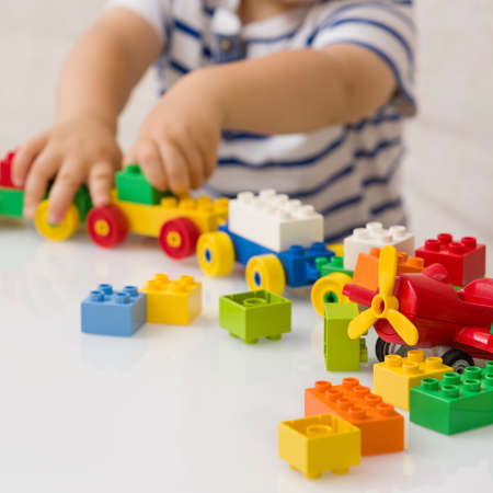 Close up of child's hands playing with colorful plastic bricks at the table. Toddler having fun and building out of bright constructor bricks. Early learning.  stripe background. Developing toys Banque d'images