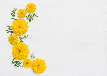 top view on beautiful yellow summer flowers on white wooden background.