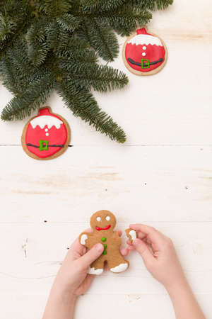 Top view on childs hands holding homemade gingerbread man on white wooden background with spruce branches and decorations. Christmas, holidays, celebration. Baking at home.