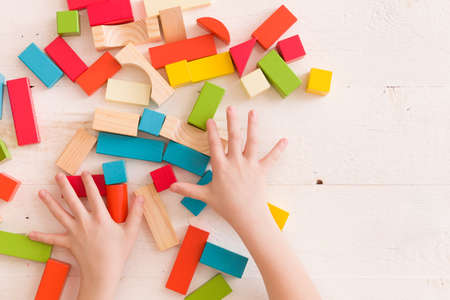 Top view on child's hands playing with colorful wooden bricks on the white table background.Kid building with geometric shapes. Learning and education concept.