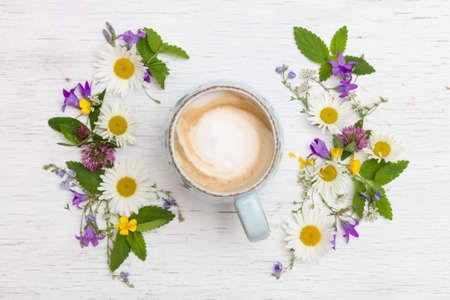 Top view on beautiful wild flowers  in shape of wreath and a cup of cappuccino coffee on white wooden background.  Summer flowers, leaves, petals and coffee on the table. Flat lay Stock Photo