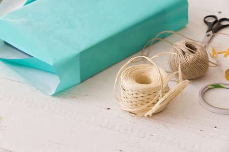 Closeup of gift ribbon, twine, tape and present wrapped in turquoise gift paper on white wooden background. Christmas, birthday or any other celebration preparations. Reklamní fotografie