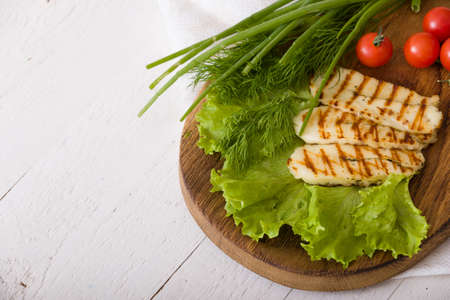 Grilled slices of homemade halloumi cheese with green salad, fresh herbs and organic tomatoes. Fried halloumi cheese with grill marks on white wooden background, top view Stock Photo