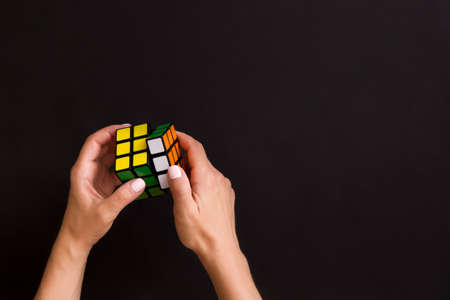 Moscow, Russia, August 24 2017: Rubik's cube in woman's hands, closeup, top view, black background. Girl holding Rubik's cube and playing with it.