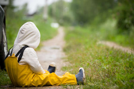 Portrait of small toddler boy in yellow rubber rain pants sitting on countryside road. Upset child. After rain. Outdoors