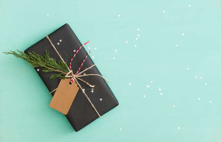 Top view on Christmas or birthday gift wrapped in black paper and decorated with craft tag, twine and tree brunch. Present on turquoise background with silver sparkling stars.