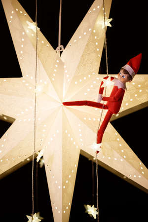 Funny Christmas toy hanging on paper star and garland on black background. Stock Photo