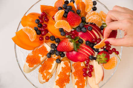 Top view on plate with juicy fruits and tangerine slice in womans hand. Organic apples, tangerines, persimmon, blueberry, red currant, strawberry and bread with red caviar - dessert or snack. Stock Photo