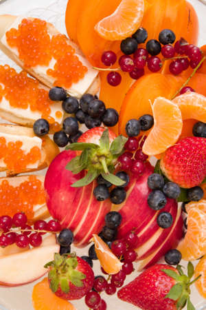 Closeup on assortment of juicy fruits on white plate. Organic apples, tangerines, persimmon, blueberry, red currant, strawberry and bread with red caviar - dessert or snack. Stock Photo