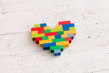 Bright heart made of  colorful plastic bricks on wooden background or table. Creative building out of bright constructor bricks. Early learning. Developing toys Stock Photo