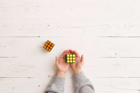 Moscow, Russia, February 16 2018: Rubik's cube in girl's hands on white wooden background. Girl holding Rubik's puzzle toy and playing with it.