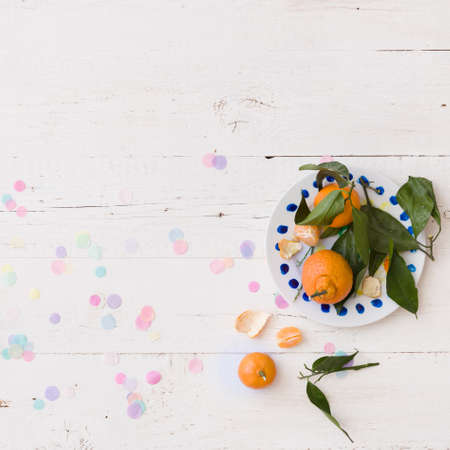 Top view on plate with tangerines on white wooden table with confetti. Closeup