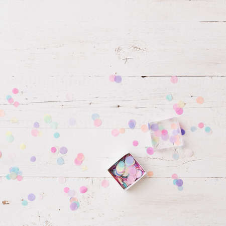 Top view on box full of colorful confetti on white wooden table or background.