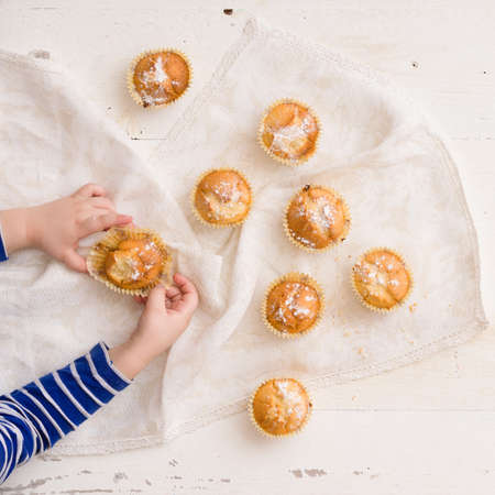 Top view on childs hands holding homemade muffin. Boy taking baked muffin from wooden board.