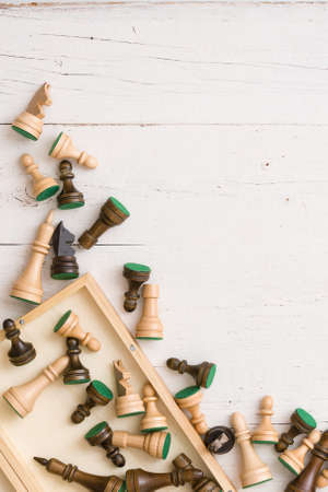 Wooden chess figures on white table background. Top view.