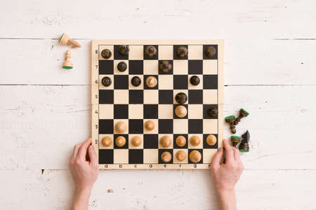 Top view on wooden chess board with figures during the game and mans hands on white wooden table background