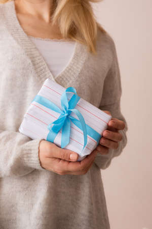 Closeup of young girls hands with nicely wrapped in white paper and decorated with blue ribbon Christmas, birthday or any other celebration gift.