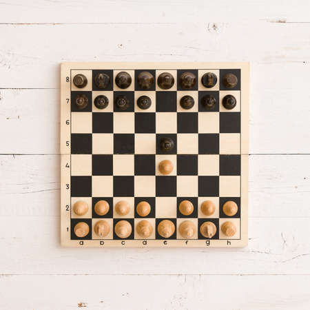 Top view on wooden chess board with figures on white wooden table background. First chess move. Stock Photo