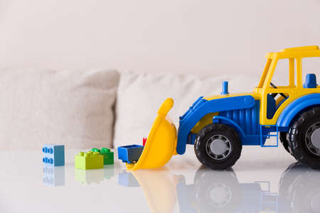 Children toy tractor with colorful plastic bricks on white background. Babys toys on the table isolated.