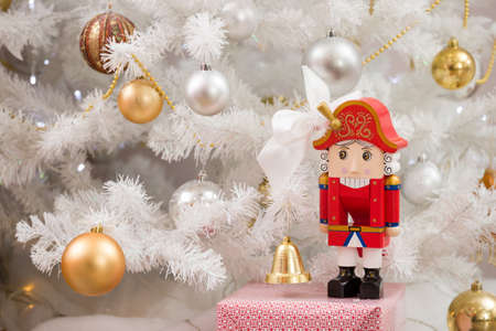 Nutcracker toy stands under the tree with christmas balls. New Year. Christmas tree branch. Holiday season