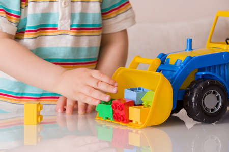 Closeup of toddler boy playing with colorful plastic bricks or details and a toy tractor. A child plays with a car in a nursery or preschool.