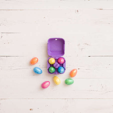 Top view on colorful pastel Easter eggs decorations on White wooden table background. Spring season. Stock Photo