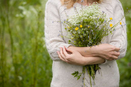 Closeup of girlss hands with bunch of wild flowers. Stock Photo