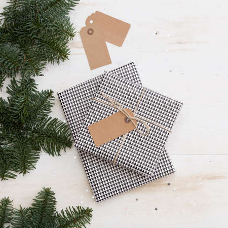 Closeup of nice Christmas gift box with tag. New Year present in black and white box with fir branches on old white wooden table or background. Celebration, holiday season and winter concept